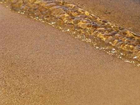 coast line: Wave on a sandy line of coast. Macro Stock Photo