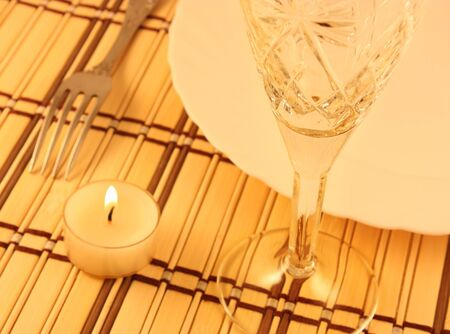 Plate, fork and wineglass on a bamboo placemat.