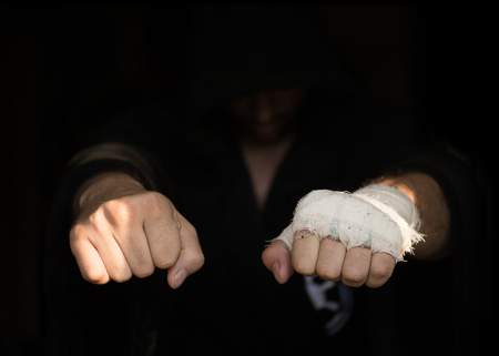 Professional taping. Hands of Pro boxer with bandage on the fists before fight. Professional fighter is prepared in the locker room before fight