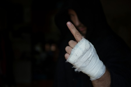 Hand of Pro boxer with bandage on the fists before fight. Professional fighter is prepared in the locker room before fight, selected focus