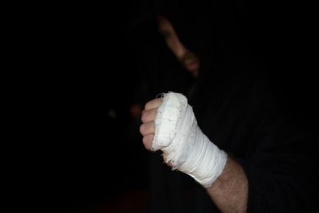 Professional taping. Hand of Pro boxer with bandage on the fists before fight. Professional fighter is prepared in the locker room before fight Reklamní fotografie
