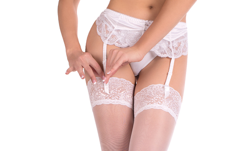 Female thighs in white sexy garter belt, stockings and lace panties. Close up, isolated on white