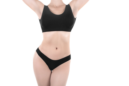 Female cropped fit body in black panties and top, isolated on white.