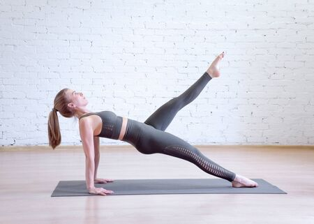 Caucasian woman doing reverse plank on mat in pilates studio, one leg up, side view. Imagens - 132070067