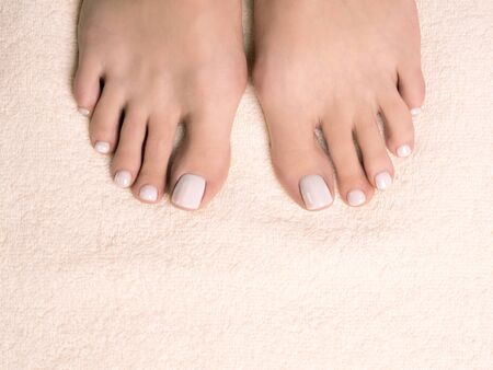 Female bare feet, toes with white pedicure on ivory terry towel, close up.