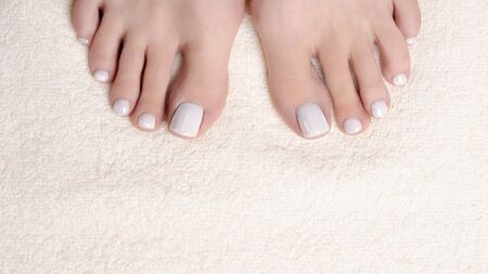 Female toes with white pedicure on ivory terry towel, close up. Woman bare feet. Reklamní fotografie