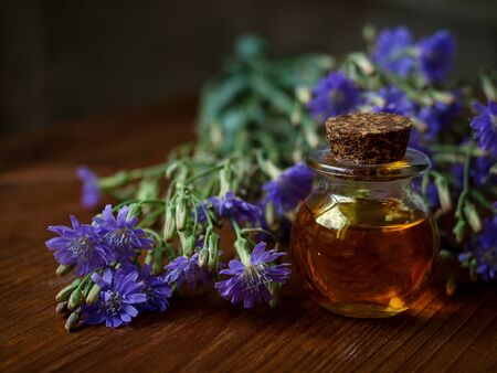 Small bottle of natural essential oil among blue flowers on wooden background. Organic cosmetic products, low key, selective focus