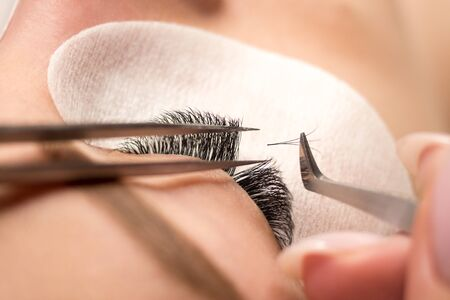 Eyelash extension procedure. Female eye with long black eyelashes, close up, selective focus.