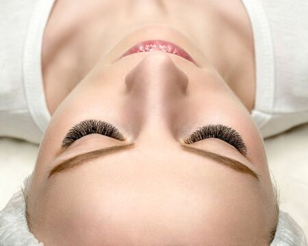 Woman face with eyelash extensions, well groomed skin, top view, close up, selective focus