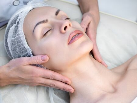 Beautician doing facial massage by hands in beauty parlour. Female face in disposable cap with closed eyes. Woman lays on a couch and relaxing. Selective focus.