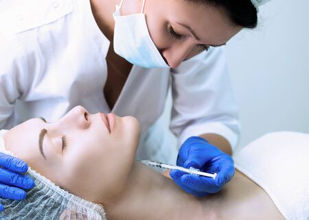 Beautician at work in beauty parlour in uniform outfit with face of patient and a disposable syringe in hand. Client lays on a couch with closed eyes and ready for procedure. Stock Photo