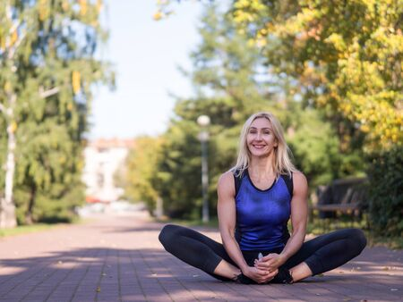 Smiling woman sitting on the pavement and stretching outdoor in urban park, selective focus Standard-Bild - 132242250