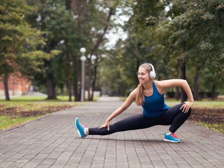 Smiling girl in the headphones doing stretching before jogging in the park outdoor, selective focus Standard-Bild - 132242253