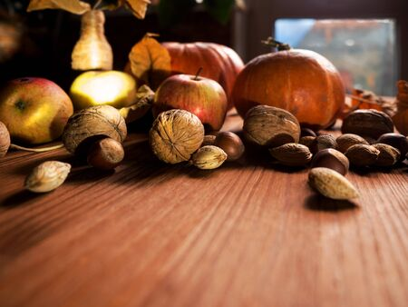 Autumn still life: pumpkins, apples, nuts and dry leaves on wooden background, fall harvest, selected focus.