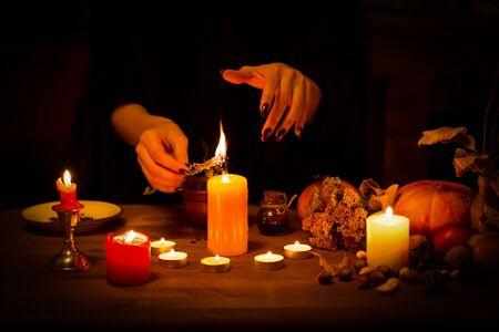 La bruja quema una hierba en el altar en la oscuridad. Manos femeninas con uñas negras afiladas hacen magia entre velas, calabaza, nueces, hojas secas, enfoque seleccionado, clave baja Foto de archivo