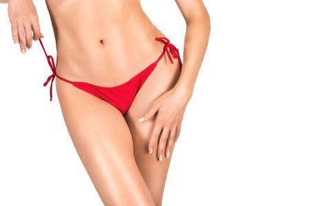 Sexy vrouwelijk lichaam in rood slipje, gebruinde huid, bikinilijn epileren, geïsoleerd op wit