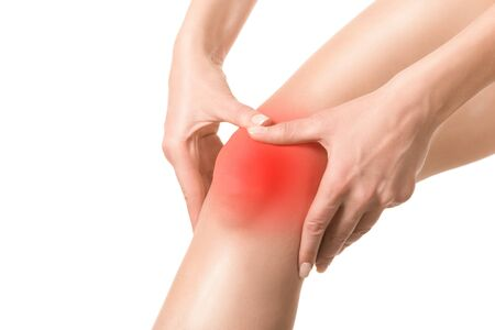 Female injured knee joint. Sore spot highlighted by red marker. Woman touches her leg by hands. Well groomed skin, close up, isolated on white