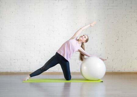 Caucasian girl practise pilates with big fit ball, attractive posing in fitness studio, lifestyle, selective focus.