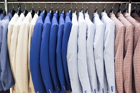 Hanger with multicolor male jackets hanging in a row in a department store. Casual clothes, menswear, trendy outfit and shopping concept