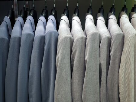 Hanger with male formal suits hanging in a row in a department store. Business clothes, menswear, trendy outfit and shopping concept Stock Photo