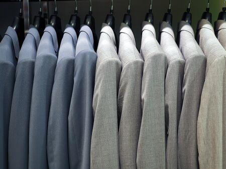 Kleiderbügel mit männlichen formellen Anzügen, die in einer Reihe in einem Kaufhaus hängen. Businesskleidung, Herrenmode, trendiges Outfit und Shoppingkonzept Standard-Bild