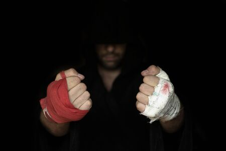 Different kinds of hands taping before rumble. Fists of pro boxer in hoodie, close up, low key, selected focus. Sport, boxing, single combat, training, power, punch, battle and preparation concept Reklamní fotografie