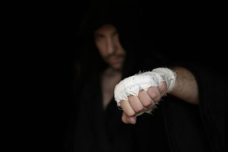 Pro caucasian fighter in hood shows punch gesture with one taping hand before rumble, low key, selected focus. Sport, boxing, single combat, training, power, punch, battle and preparation concept