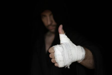 Boxer in robe shows gesture thumb up with his taping hand before fighting, low key, selected focus. Sport, boxing, single combat, training, power, punch, battle and preparation concept Reklamní fotografie