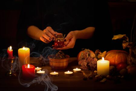Witch makes some potion, spell and collects ingredients on the altar in the dark. Female hands with sharp black nails among candles, pumpkin, nuts, dry leaves, magic herbs, selected focus, low key. Halloween, Yule, witchcraft, voodoo, fortune telling and divination concept