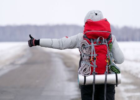 Travel hitch hiker holding thumb up on secondary road to share a ride. Winter time, back view, selected focus.