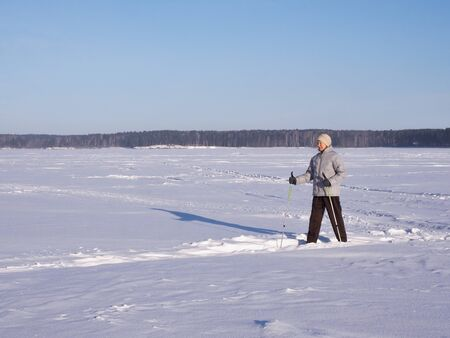Elderly woman doing Nordic walking in winter sunny day on a snow-covered lake, outdoor.
