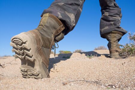 Human feet in hiking rough boots stepping on the sand in a desert, close up, wide angle, selected focus Foto de archivo
