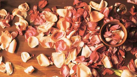 Aroma oil bottle and clay bowl among roses petals on wooden surface, toned warm, top view, selected focus