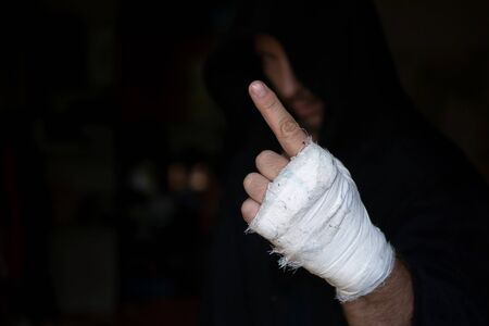 Pro boxer in hood shows warning gesture with one taping hand before rumble, low key, selected focus. Sport, boxing, single combat, training, power, punch, battle and preparation concept