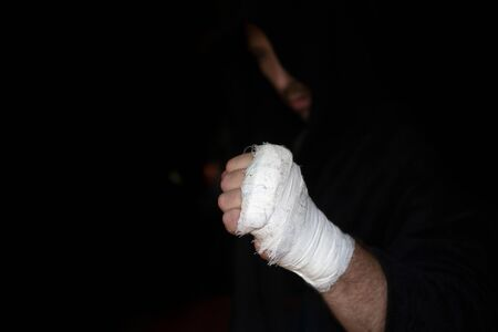 Boxer in hood shows one taping fist before rumble Reklamní fotografie
