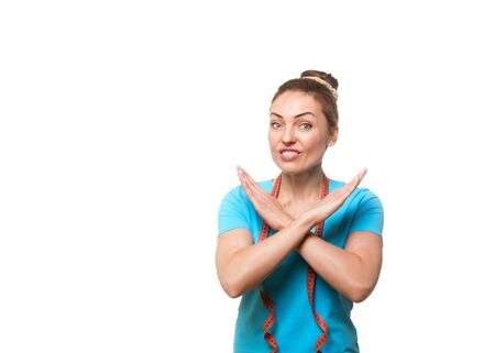 Fitness trainer wrinkles her nose and does forbidding gesture with hands.