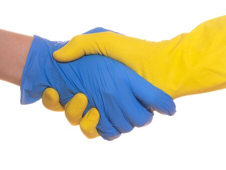 Safe contact. Two people shaking hands in rubber protective blue and yellow gloves, close up, isolated on white.
