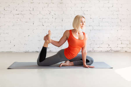 Yoga, pigeon pose. Young fit caucasian woman does leg stretching sitting on a mat, in loft white studio indoor, selective focus.