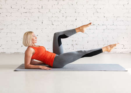 Pilates, abs workout. Attractive fit caucasian woman does practice sitting on a mat, in loft white studio indoor, selective focus.