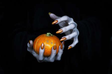 Small pumpkin in witches knotty hand. Scary undead pale fingers with long sharp claws in the dark, low key, selected focus.