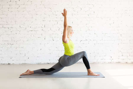 Attractive adult caucasian woman practice balance drill in deep lunge with hands up on a mat in loft white studio indoor, selective focus. Standard-Bild