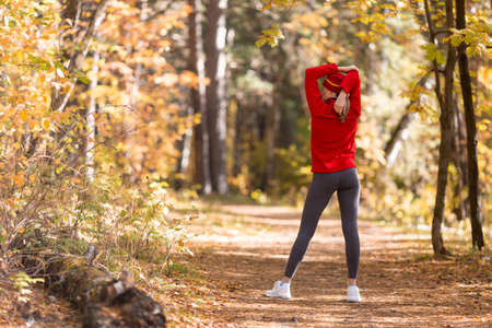 Caucasian fit slim woman in red sportswear and a cap warning up her arms and joints before workout in the park in autumn, back view, selective focus Imagens