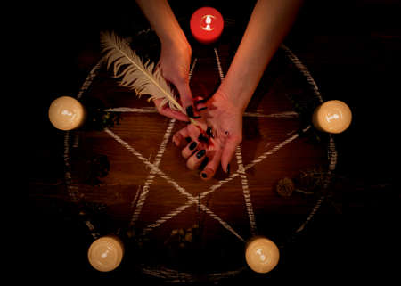 Female bleeding hand on the altar in the dark. Witch carry out a black magic ritual using her own blood, pentagram, pen, candles, feathers, dry herbs on wooden surface, low key, selected focus. Stock Photo