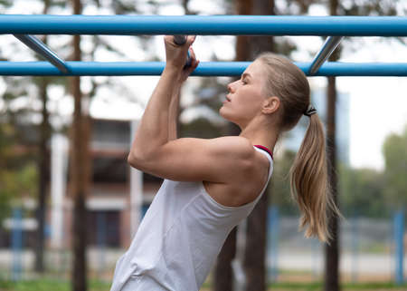 Athletic blond beautiful caucasian woman doing chin ups exercise on the sports ground outdoor in summer, side view, close up, selective focus