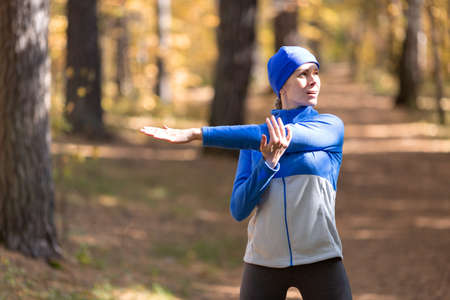 Caucasian adult woman in blue sportswear and a cap warm up her triceps and joints before jogging in the forest in autumn, half-length portrait, selective focus