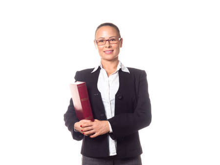 Attractive intelligent smiling adult woman as a coach in formal wear and eyeglasses with a big book under her arm, isolated on white.