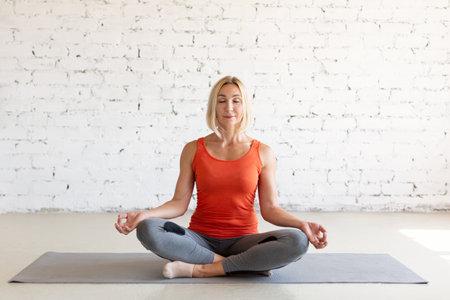 Adult fit caucasian woman practice meditation in classic pose on a mat in loft white studio indoor, yoga practice, selective focus. Standard-Bild