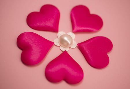 Many pink hearts are laid out in the form of a flower on a pink background. Valentines Day