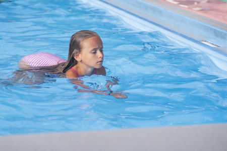 Beautiful little girl swims in the pool , cute little girl in pool in sunny day.little girl .