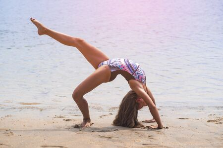 schoolgirl making gymnastics on seashore Banque d'images